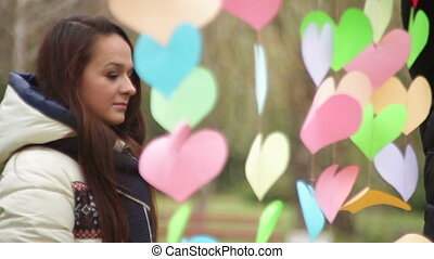 Man hangs colored hearts on Valentines Day
