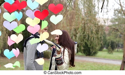 loving couple standing near a multi-colored hearts on...