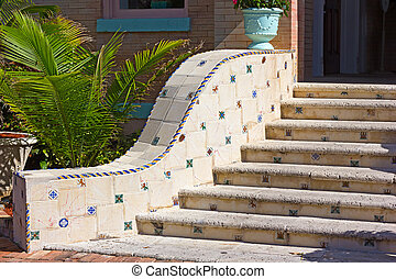 Details of wide steps with mosaic tiles. Colorful steps with light blue vase.