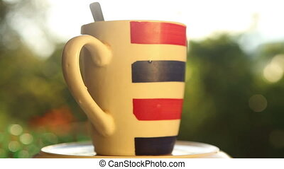 striped cup with coffee on rotated plate on a backlit