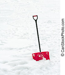 Red plastic shovel with black handle stuck in fluffy snow -...