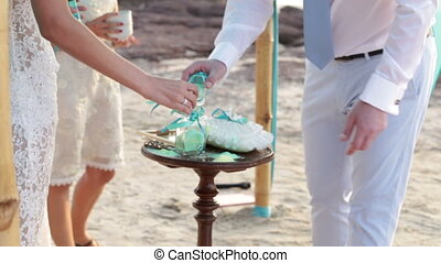 Bride and groom pour into pot multicolored sand - Bride with...