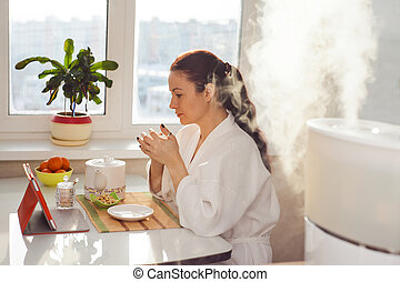 Woman drinking tea reading tablet at humidifier - Woman...