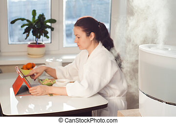 Woman sitting with tablet PC on the background of humidifier...