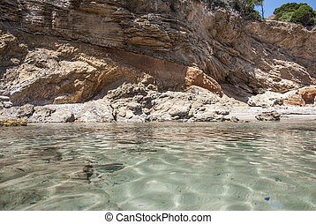 A transparency sea with a rocks beahind in Sardinian beach