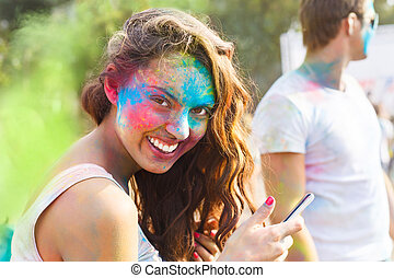 Portrait of happy young girl on holi color festival using...