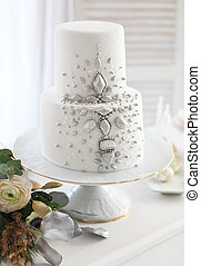 White wedding cake with silver decoration and wedding...