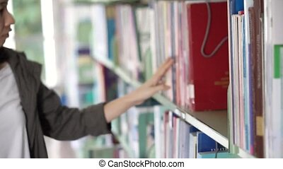 Girl in library looking for book
