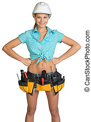 Pretty girl in helmet, shorts, shirt and tool belt with tools