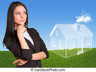 Businesswoman looking at imaginary house. Green lawn and sky...
