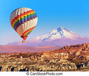 Balloon over Cappadocia - Balloon flying over rock landscape...