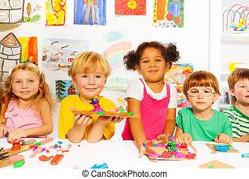 Happy kids with modeling clay in classroom - Large group of...