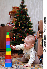 baby try to pull down colorful pyramid at home
