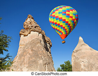 Cappadocia. - Hot air balloon flying over rock landscape at...