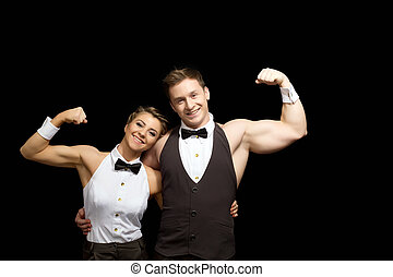 Smiling dancers shows biceps, isolated on black