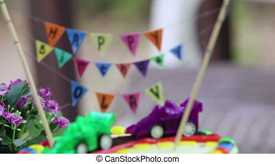 creamy cake decorated with toy cars and inscription Happy...