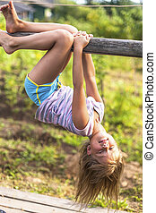 Little girl having fun in park hanging upside down on green rural countryside.