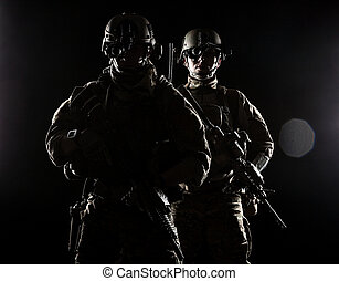 United States Army rangers with assault rifles on dark...