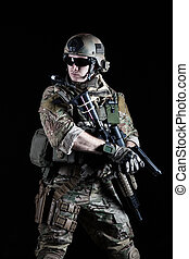 United States Army ranger with pistol on dark background