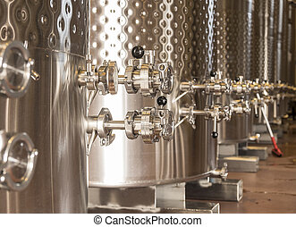 Winery Fermentation Tanks - A row of fermentation tanks in a...