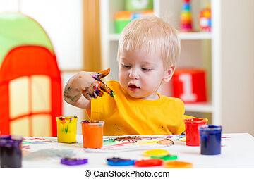 kid painting at home - cute kid boy painting at home or...