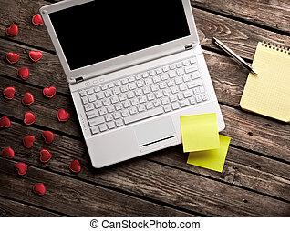 White laptop and hearts with sticky notes and notepad on old...