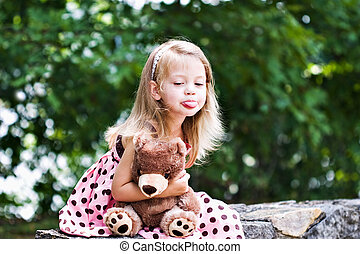 Child sticking out her tongue - Cute, naughty child holding...