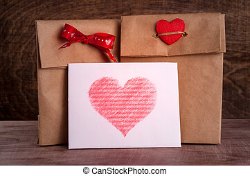 Two gifts in paper bags with bowknot and heartWhite card...