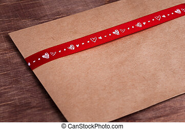 Yellow envelope wrapped in red ribbon with heartsValentines...