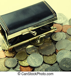 Black purse with coin of different countries - the concept...