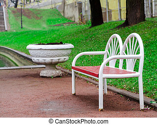 red-white wooden bench in the park on the green grass background