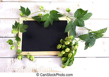 Blackboard with hops on wooden ground