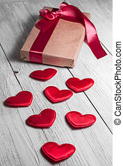 Gift tied with ribbon and red heart on white wooden...