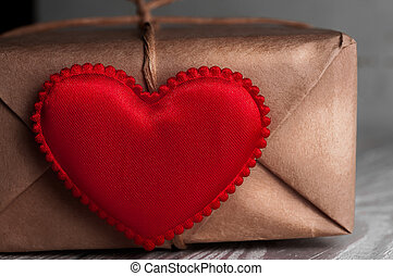Gift Packed in paper and tied with string with red heart on...