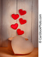 Red hearts departing from the magic box, on white wooden...