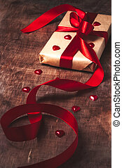 Gift tied with ribbon and red heart on wooden background...