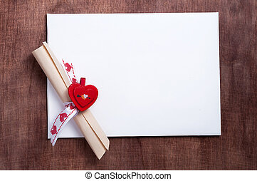 Valentines day White card with a small red heart on wooden...