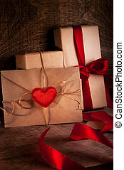 Gifts wrapped with a red ribbon A letter with a red heart...