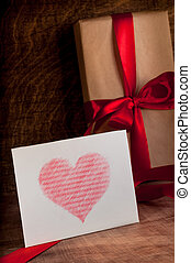 Gifts wrapped with a red ribbonWhite card with a red...