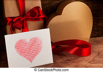 Gifts wrapped with a red ribbon and cardboard heartWhite...