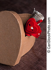 Cardboard heart and a roll of fabric tied with...