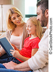 Reading their favorite book together Happy family of three...