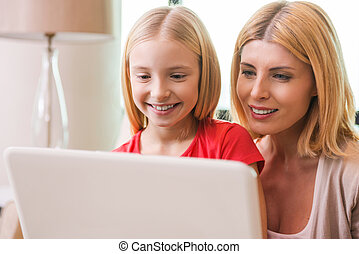 Surfing the net together. Happy mother and daughter bonding...