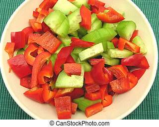 Slices of cucumber and red pepper in a ceramics bowl