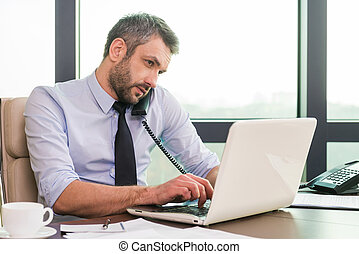 Very busy. Confident mature man in shirt and tie working at...