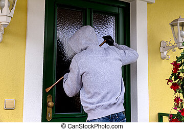 burglar at a house door - a burglar trying to break a door