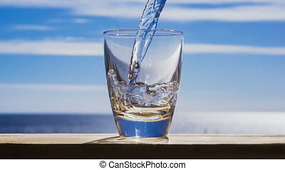 Blue water is flowing into the glass forming bubbles and...