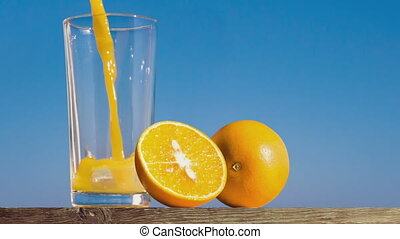 pouring a glass of orange juice creating splash isolated on...