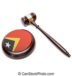 Judge gavel and soundboard with national flag on it - East...