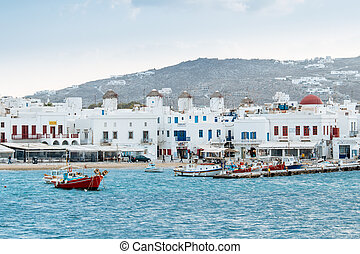 Greek fishing boats in the port of Mykonos with windmills in...